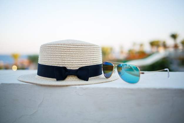 Zomerhoed en bril voor dames liggen op het terras met uitzicht op zee