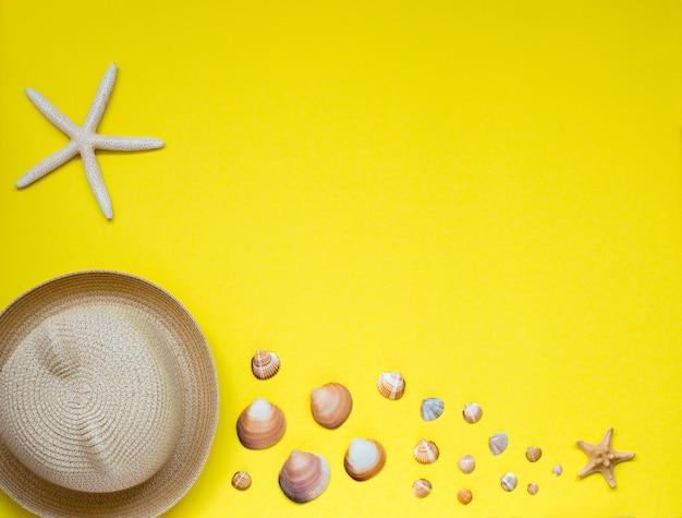 Zomerhoed en een selectie van schelpen en zeesterren, gelegen op geel.