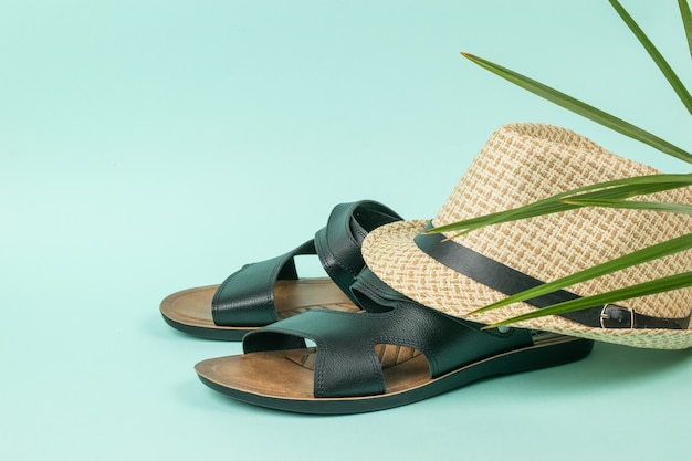 Zomerhoed voor heren op zwarte sandalen op een blauwe achtergrond. zomer herenschoenen.