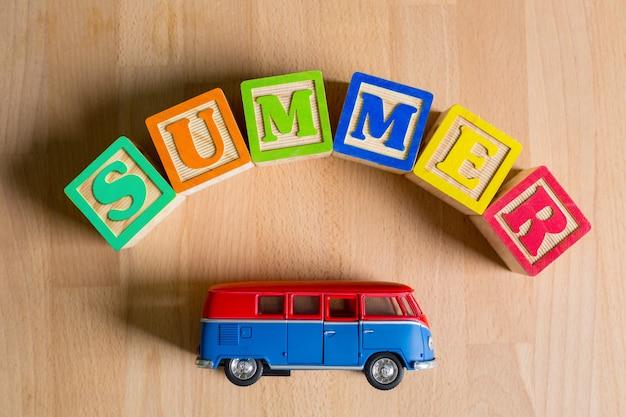 Zomerkubustekst met speelgoedbusje voor uw vakantie.
