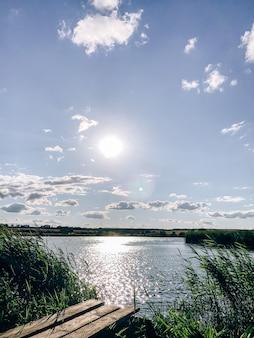 Zomerlandschap aan de oever van een vijver in de ondergaande zon