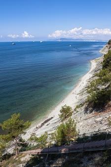 Zomerlandschap een trap naar de zee op de rotsen leidt naar een wild strand