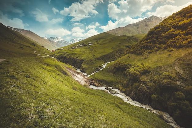 Zomerlandschap met rivier en berg besneeuwde piek shkhara zemo, kazbegi nationaal park, georgië. groene heuvels en kleine bergrivier in de uitlopers van de kaukasus. vintage instagram kleurfilter toning