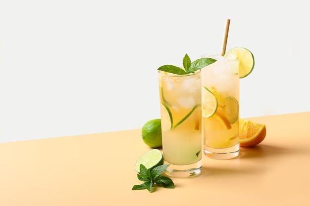 Zomerlimonade of cocktail met sinaasappel en limoenschijfje op een verfrissend drankje als achtergrond met kleur