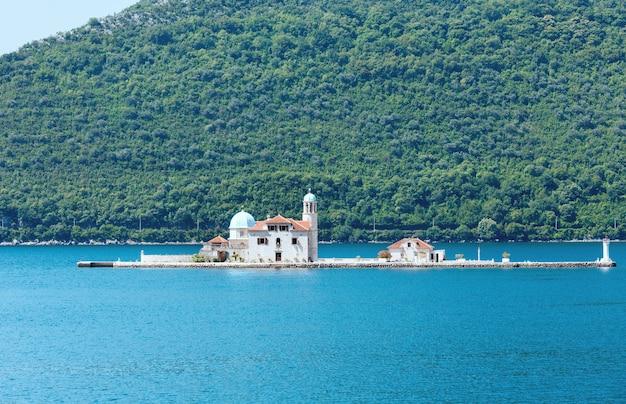 Zomermening op kunstmatig eiland met rooms-katholieke kerk van onze-lieve-vrouw van de rotsen. gebouwd in 1632y. (perast stad, montenegro, kotors baai)