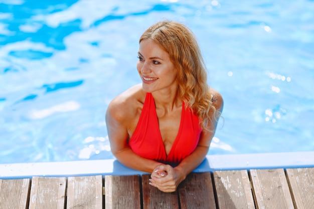 Zomermode. vrouw in rode zwembroek bij zwembad.