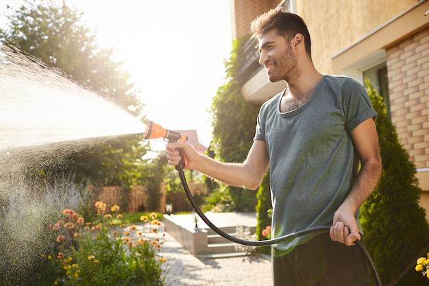 Zomerochtend in plattelandshuis. portret van jonge aantrekkelijke tan-huid bebaarde man in blauw t-shirt glimlachen, planten water geven met slang, werken in de tuin.