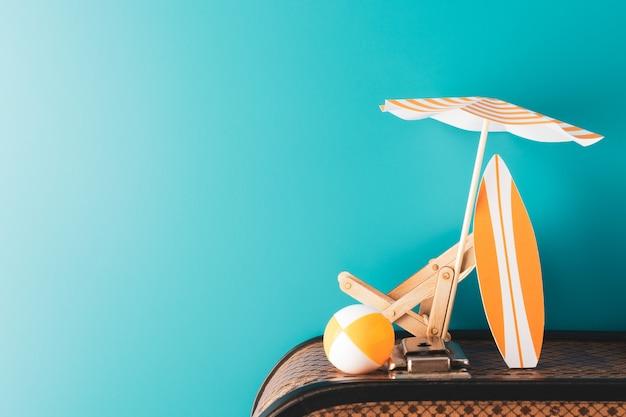 Zomerparaplu met houten chaise longue oranje surfplank en opblaasbare bal op bagage op blauwe achtergrond