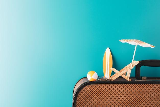 Zomerparaplu met houten chaise longue oranje surfplank en opblaasbare bal op bagage
