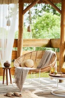 Zomerpaviljoen aan het meer met stijlvolle rotan fauteuil, salontafel, bank, kussens, plaid en elegante accessoires in een moderne inrichting. zomerse vibes. ontspan.