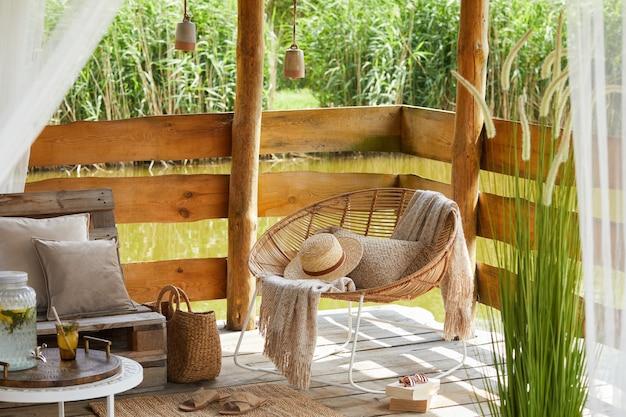 Zomerpaviljoen aan het meer met stijlvolle rotan fauteuil, salontafel, bank, kussens, plaid en elegante accessoires in een moderne inrichting.