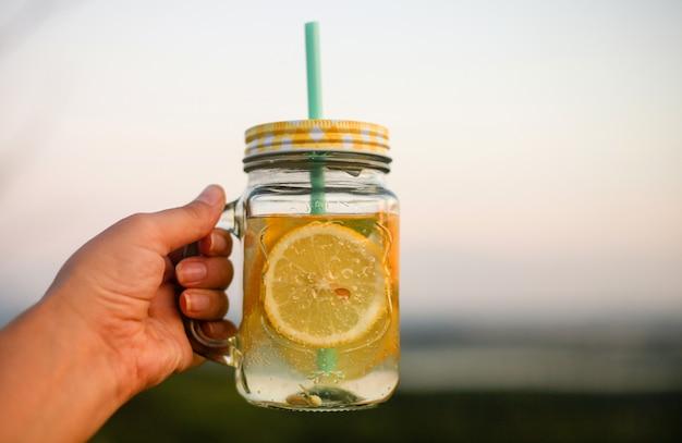 Zomerpicknick buitenshuis, zomer drankje pot met limonade, in de hand