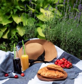 Zomerpicknick in lavendelveld. stilleven zomer buiten picknick met bessen, strohoed en sap