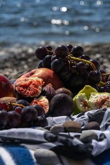 Zomerpicknick met vijgen, druiven en appels. zee en plaid op een strand