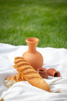 Zomerpicknick op het groene gras. kleikruik en brood