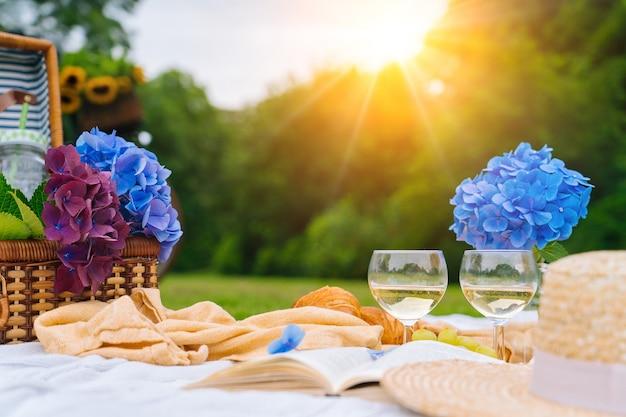 Zomerpicknick op zonnige dag met brood, fruit, boeket hortensiabloemen