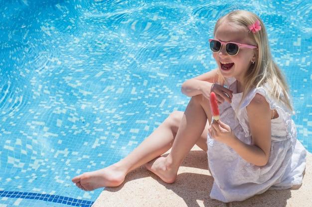 Zomerplezier. gelukkig meisje eet ijs in de buurt van het zwembad