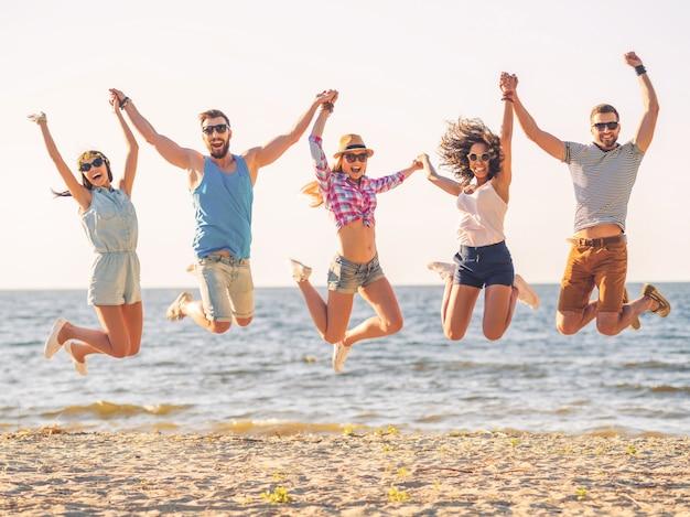 Zomerplezier. groep gelukkige jonge mensen hand in hand en springen met de zee op de achtergrond