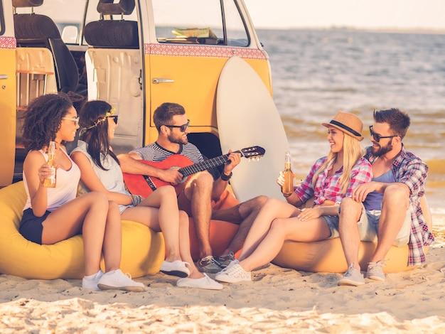 Zomerplezier. groep vrolijke jonge mensen die bier drinken en gitaar spelen terwijl ze op het strand zitten in de buurt van hun retro minivan