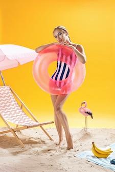 Zomerportret het blonde vrouwelijke model stellen met zwemmende ring
