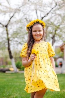 Zomerportret van een meisje in een gele jurk die in de wind vliegt met een boeket paardebloemen in haar h...