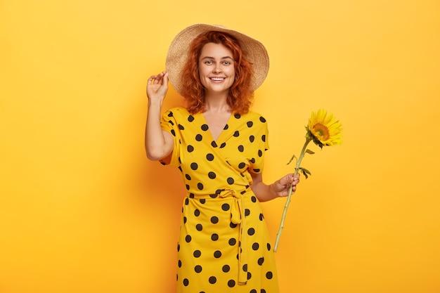 Zomerportret van glimlachende vrolijke gemberdame met tedere glimlach, stands met zonnebloem geplukt uit het veld