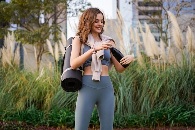 Zomerportret van mooie vrouw die alleen poseert in het stadspark na haar yoga-fitnessles