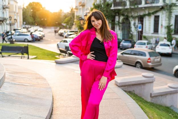 Zomerportret van speelse knappe vrouw in stijlvol roze jasje.