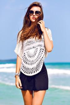 Zomerportret van stijlvolle jonge vrouw, blauwe lucht, heldere oceaan, geniet van vakantie in tropisch land, vreugde, vakantiestijl