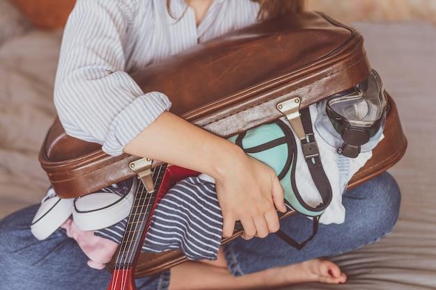 Zomerreizen en vakantie. de jonge koffer van de vrouwenverpakking thuis