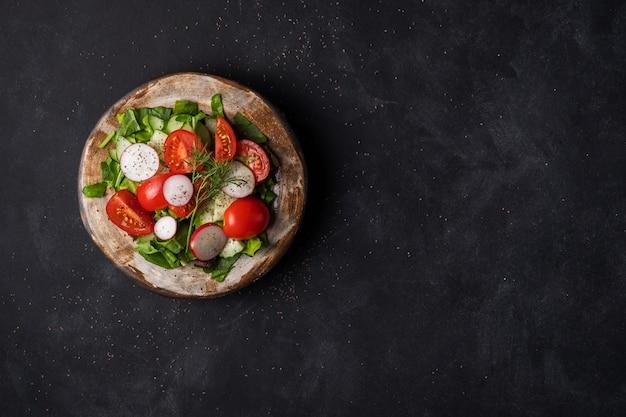 Zomersalade van spinazie, tomaten, radijs, dille op een zwarte achtergrond
