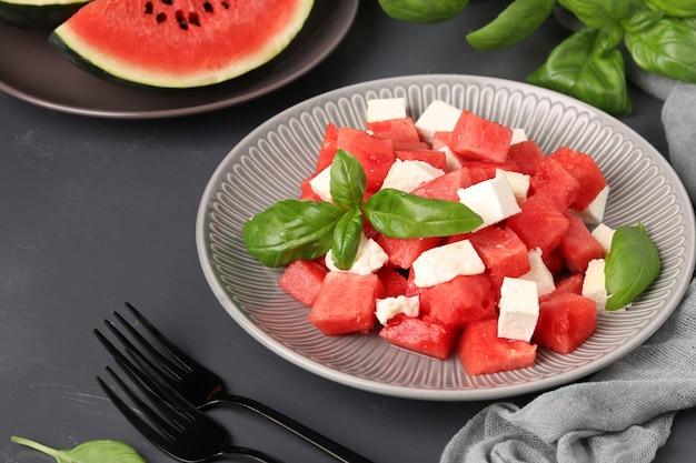 Zomersalade van watermeloen, fetakaas en groene basilicum, gezonde voeding, close-up. horizontaal formaat