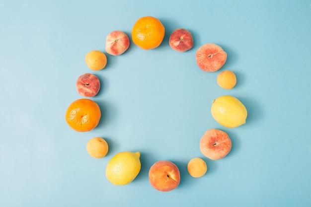 Zomersamenstelling van tropisch biologisch fruit gerangschikt in de vorm van een cirkel op een pastelblauwe achtergrond