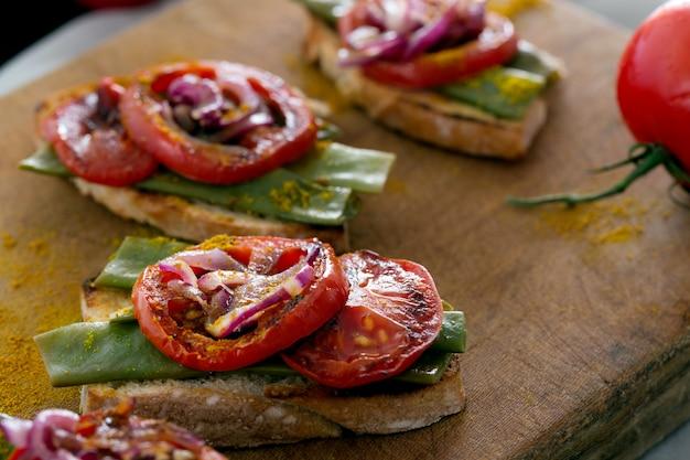 Zomersandwich bereid met gebakken rode ui, tomaat en bruine bonen