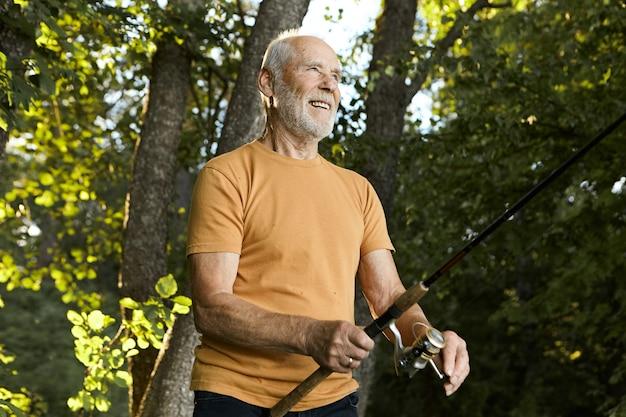 Zomerse foto van knappe energieke actieve ongeschoren senior man die met pensioen gaat mooie zomerochtend buitenshuis doorbrengen, vis vangen met behulp van een hengel, met vrolijke, vrolijke gezichtsuitdrukking
