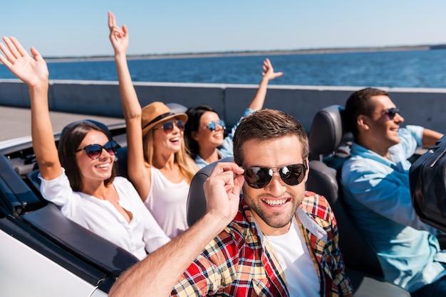 Zomerse roadtrip. groep jonge gelukkige mensen die genieten van een roadtrip in hun cabrio terwijl een knappe man zijn zonnebril aanpast en glimlacht