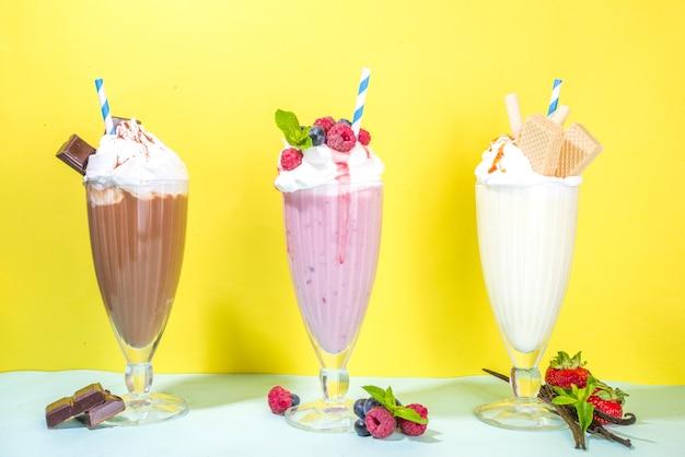 Zomerse verfrissende drankjes, milkshakes, gekke shakes met ijs, bessen, vanille, chocolade. op een helderblauwe gele achtergrond