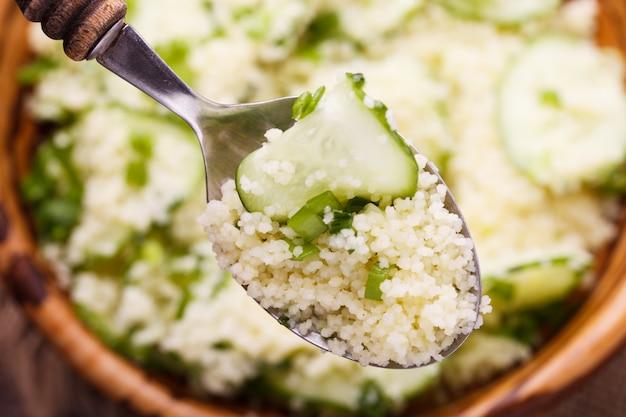 Zomersla, couscous met komkommer en groene uien.