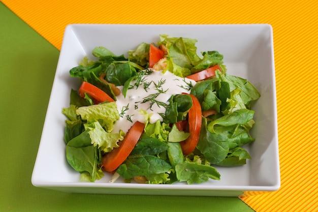 Zomersla met spinazie, door tomaten en zure room. veganistische salade