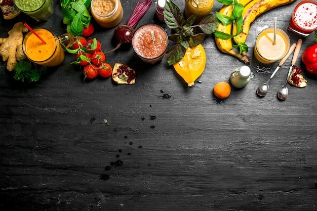 Zomersmoothies van groenten, bessen en fruit. op zwarte achtergrond.