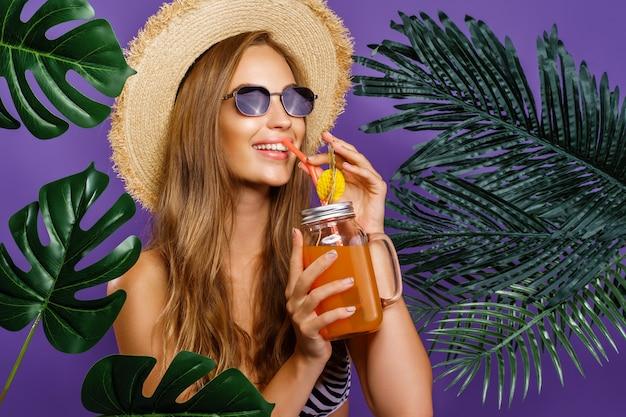 Zomerstijl portret van jonge aantrekkelijke vrouw die een zonnebril draagt die cocktail drinkt