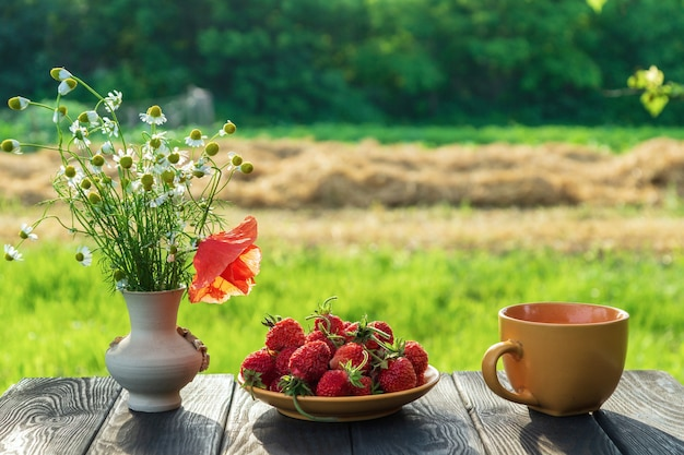 Zomerstilleven van een bord met aardbeien en koffie op een tafel met bloemen Premium Foto