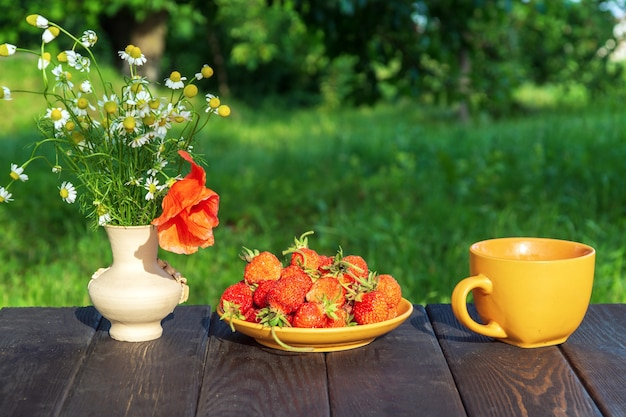 Zomerstilleven van een bord met aardbeien en koffie op een tafel met bloemen