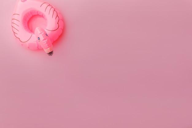 Zomerstrand eenvoudig minimaal ontwerp met opblaasbare flamingo geïsoleerd op pastelroze achtergrond