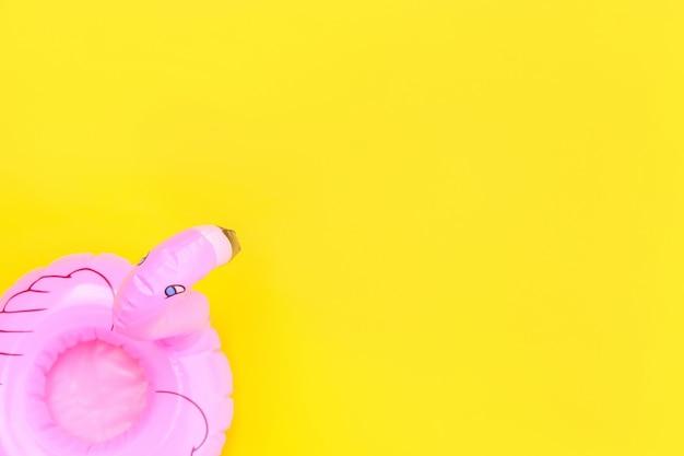 Zomerstrand eenvoudig minimaal ontwerp met roze opblaasbare flamingo geïsoleerd op gele achtergrond