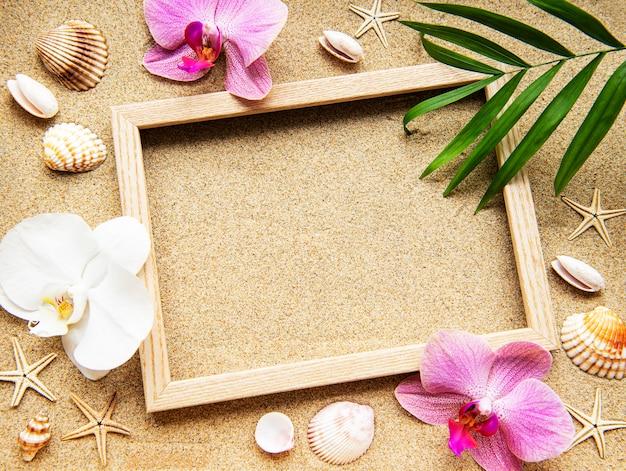 Zomerstranddecoratie: frame met orchideeën, schelpen en zeesterren op een zandoppervlak