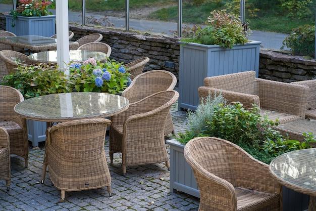 Zomerterras in hotel of restaurant met gezellige houten rieten meubels groene planten en geen mensen