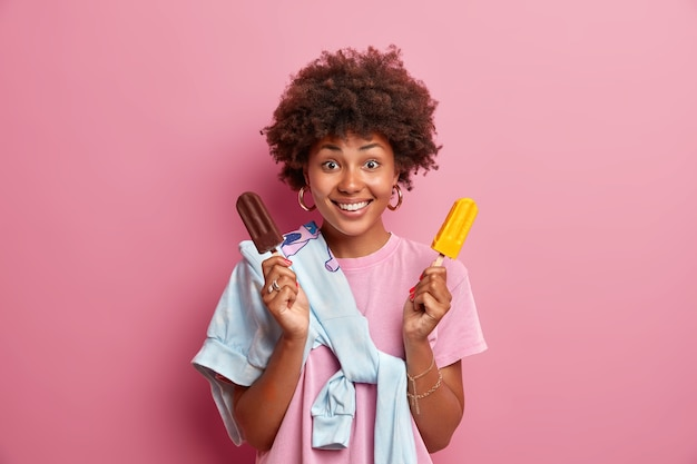 Zomertijd concept. blij dat positieve vrouw met afro-kapsel lekker bevroren ijs houdt, geniet van het eten van heerlijk koud dessert, nonchalant gekleed, poses