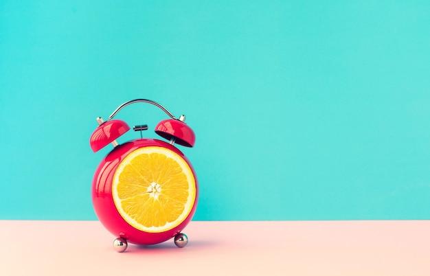 Zomertijd concepten ideeën met oranje wekker op blauwe pastel achtergrond.
