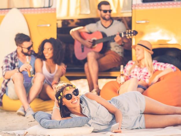 Zomertijd met vrienden. vrolijke jonge vrouw die lacht naar de camera terwijl ze in de buurt van retro minibus ligt met vrienden op de achtergrond